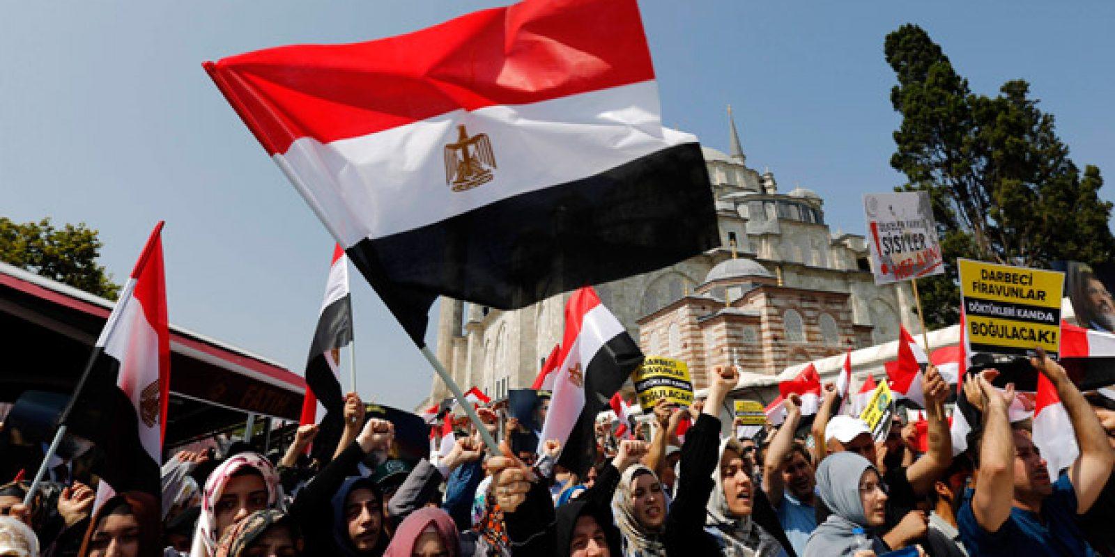 Forças de segurança egípcias usam violenta repressão para dispersar os partidários do presidente destituído Mohamed Mursi. Bandeira Egípcia é asteada durante protesto| Mohamed Nureldin Abdallah / Reuters