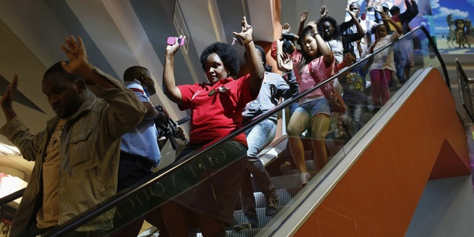 Civilians escape an area at the Westgate Shopping Centre in Nairobi. Imagen Por: Civilians escape an area at the Westgate Shopping Centre in Nairobi September 21, 2013. Gunmen stormed the shopping mall in Nairobi on Saturday killing at least 20 people in what Kenya