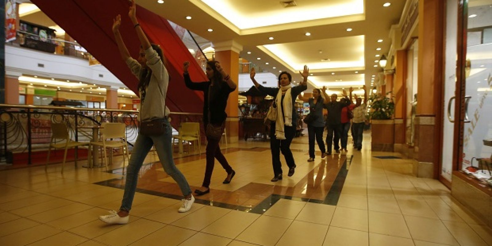 Shoppers and shop assistants raise their hands as they are escorted to safety while armed police hunt gunmen who went on a shooting spree in Westgate shopping centre in Nairobi. Imagen Por: Shoppers and shop assistants raise their hands as they are escorted to safety while armed police hunt gunmen who went on a shooting spree in Westgate shopping centre in Nairobi September 21, 2013. The gunmen stormed the shopping mall in Nairobi on Saturday killing at least 20 people in what Kenya