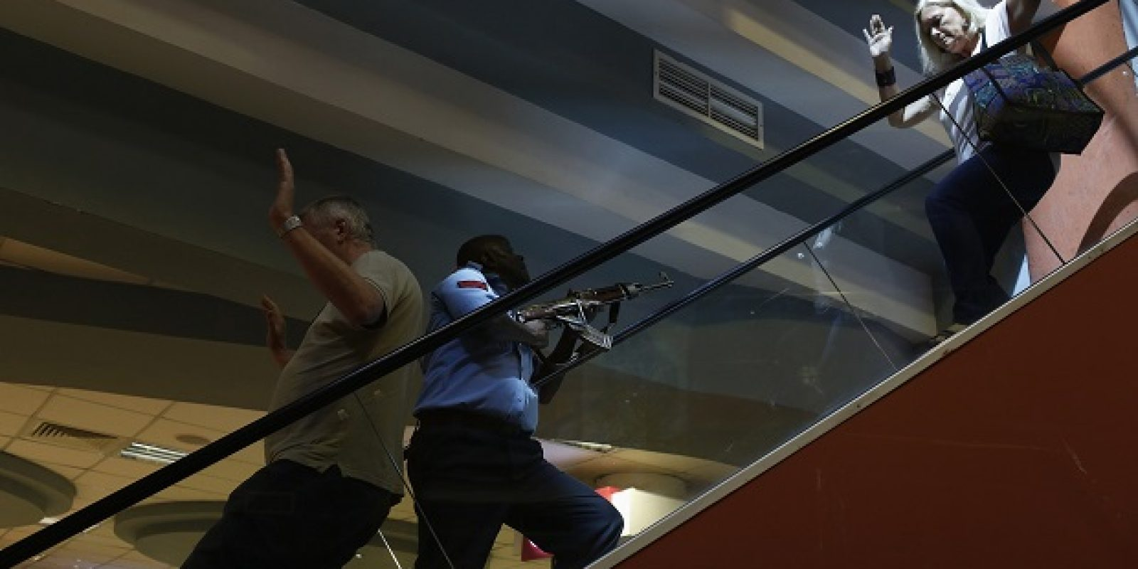 A police officer secures an area as civilians flee inside Westgate Shopping Centre in Nairobi. Imagen Por: A police officer (C) secures an area as civilians flee inside Westgate Shopping Centre in Nairobi September 21, 2013. Gunmen stormed the shopping mall in Nairobi on Saturday killing at least 20 people in what Kenya