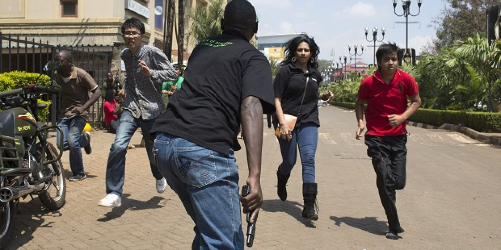 An armed security officer assists civilians escaping from the Westgate Shopping Centre where gunmen went on a shooting spree, in Nairobi. Imagen Por: An armed security officer (C) assists civilians escaping from the Westgate Shopping Centre where gunmen went on a shooting spree, in Nairobi September 21, 2013. The gunmen stormed the shopping mall in Nairobi on Saturday killing at least 20 people in what Kenya
