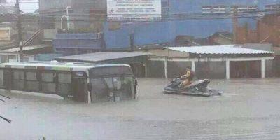 Homem-em-Jet-Ski-tenta-resgatar-passageiros-presos-em-ônibus-na-Rua-Tinguá,-em-Rocha-Miranda-Marcos-Lima-Ouvindo-Bandnews-Fluminense-FM