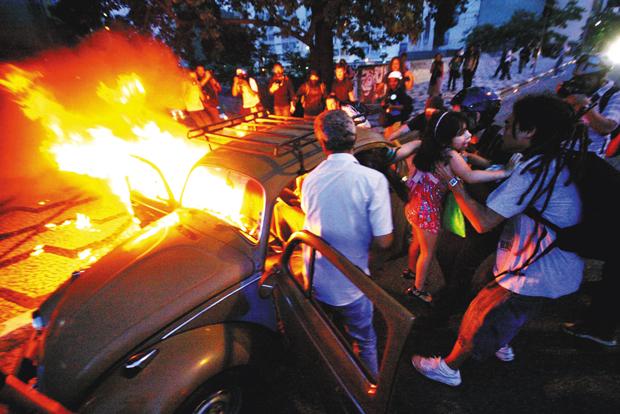 Família sai de carro incendiado durante protesto  | Aloisio Mauricio / Brazil Photo Press/Folhapress