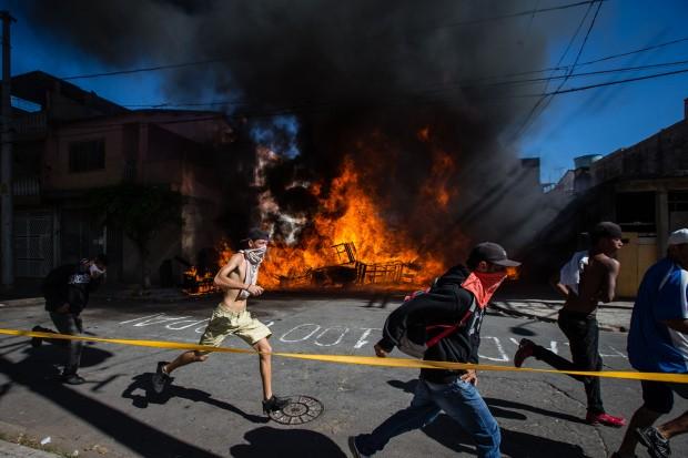 Pessoas contrárias à reintegração de posse em Itaquera passam por barricadas em chamas | Avener Prado/Folhapress