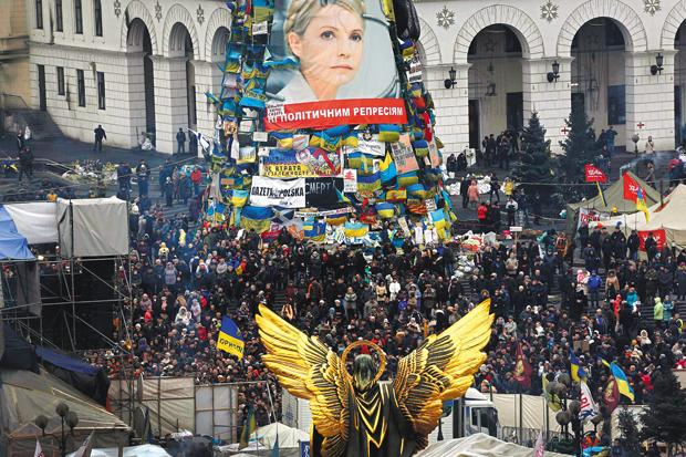 Manifestantes se reúnem na praça da Independência, em Kiev, sob imagem de Yulia Tymoshenko | Y. Behrakis/Reuters