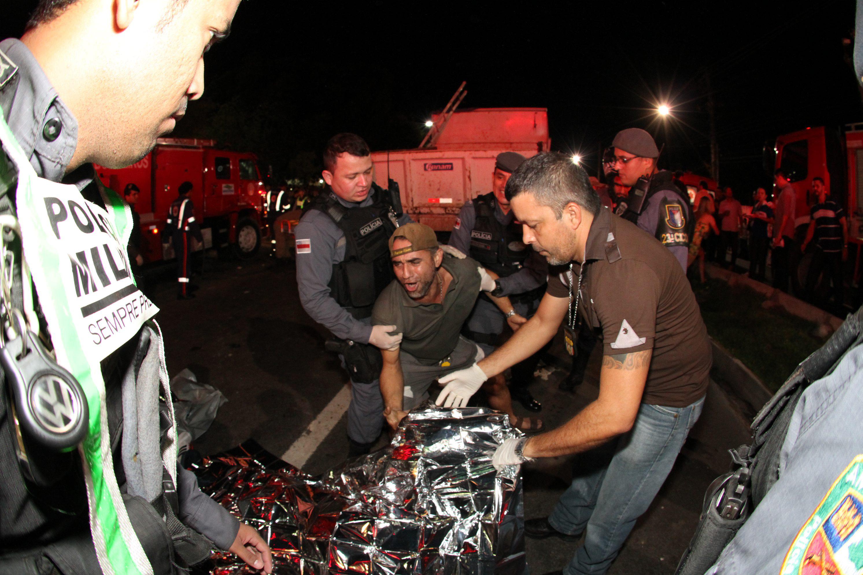 Parente de vítima se desespera e é contido por policial ao chegar ao local do acidente | Clóvis Miranda/A Crítica/Folhapress