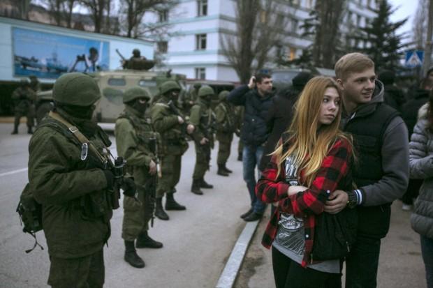 Casal diante de pelotão militar na região da Crimeia, na Ucrânia | Baz Ratner/Reuters