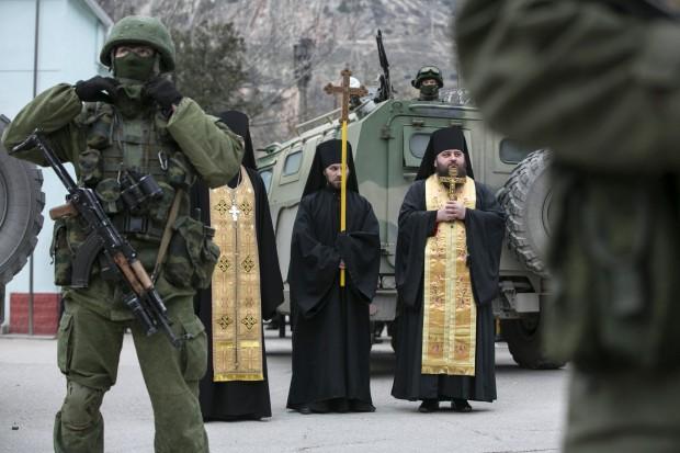 Monges ortodoxos rezam próximos de militares armados e blindados russos na região da Crimeia | Baz Ratner/Reuters