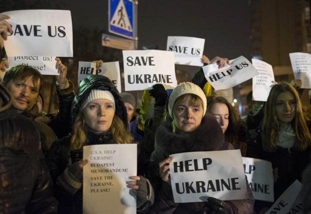 Ucranianos reunidos diante da embaixada das EUA em Kiev seguram cartazes onde se lê: ajudem a Ucrânia e Salvem a Ucrânia | Gleb Garanich/Reuters