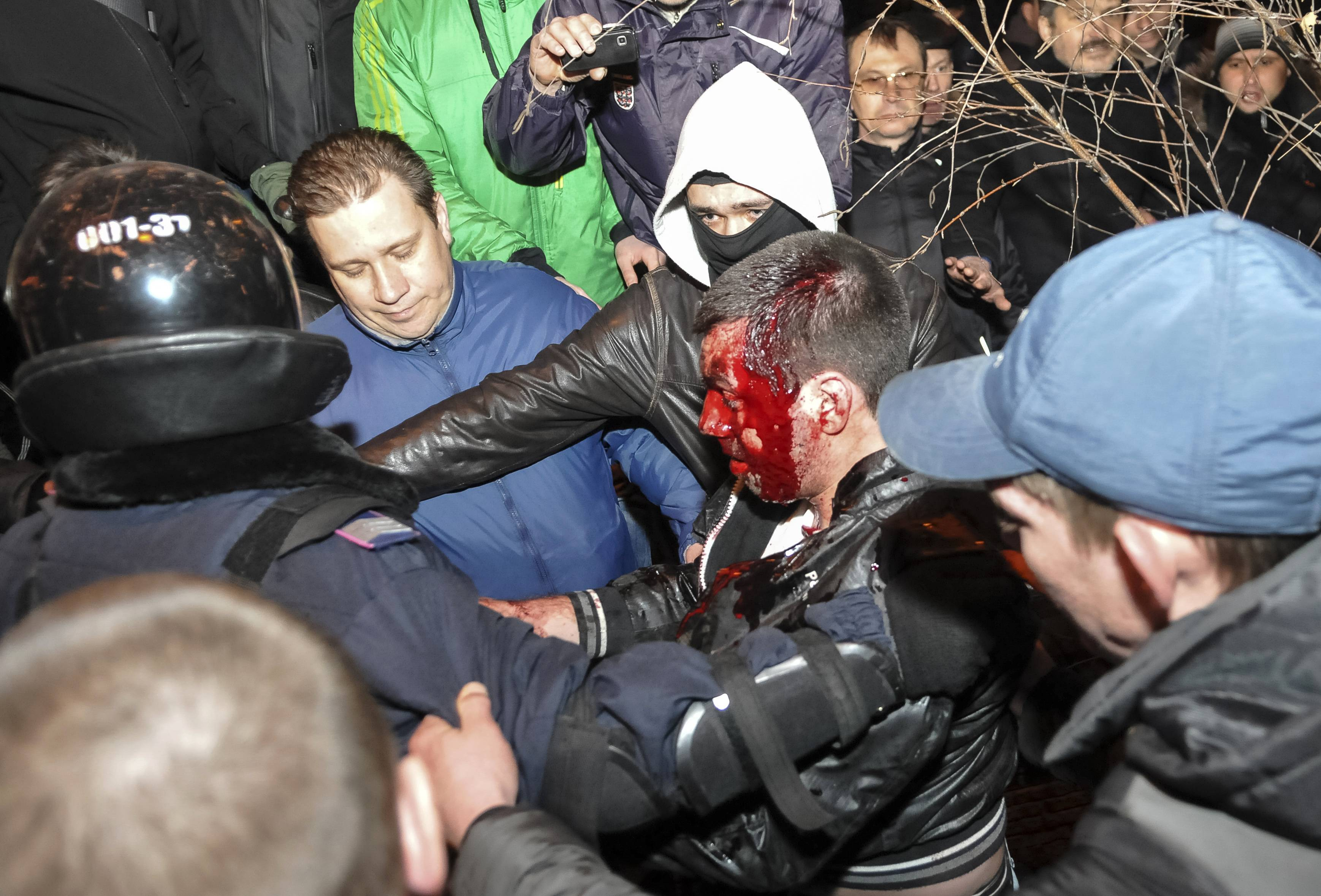 Policiais conduzem manifestante ferido em confronto na cidade ucraniana de Donetsk, onde uma pessoa morreu | Mikhail Maslovsky/Reuters
