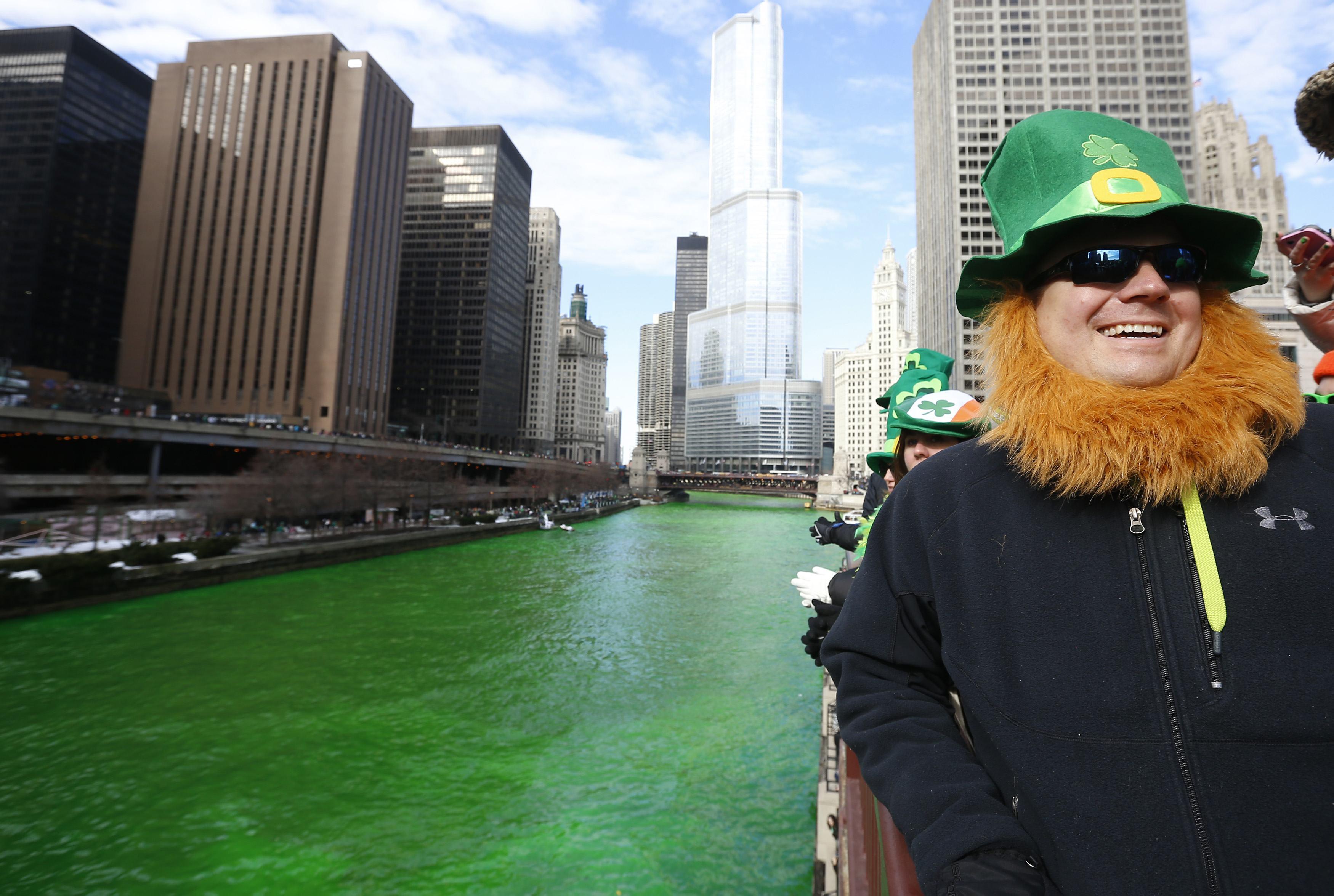 Homem vestido de duende posa para foto perto do rio Chicago, que ganha coloração verde, uma tradição da festa pelo Dia de São Patricio | Jim Young/Reuters