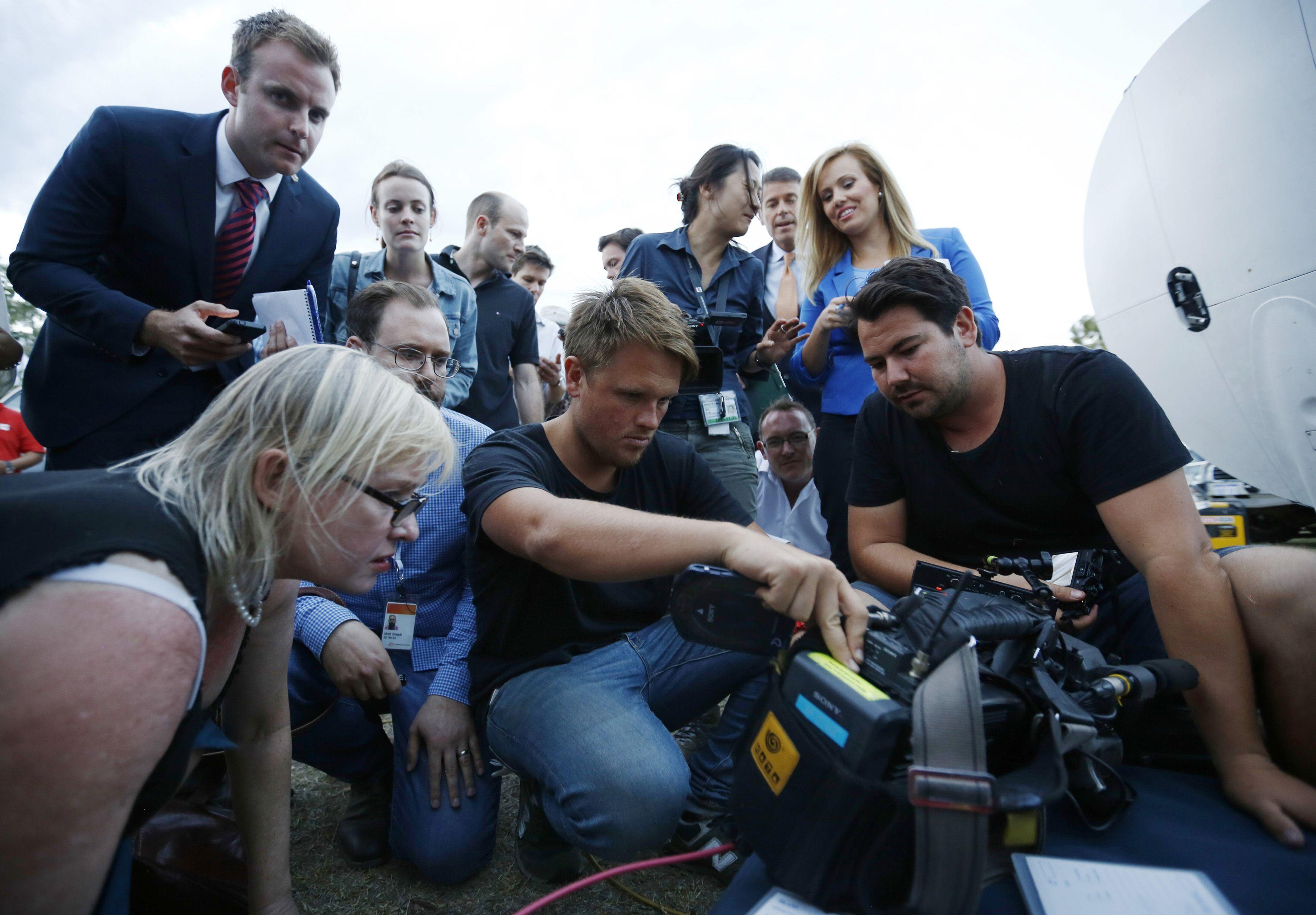 Um jornalista olha para o monitor da câmera de uma equipe de televisão que registrou cenas de objetos  no Oceano Índico | Jason Reed/ Reuters