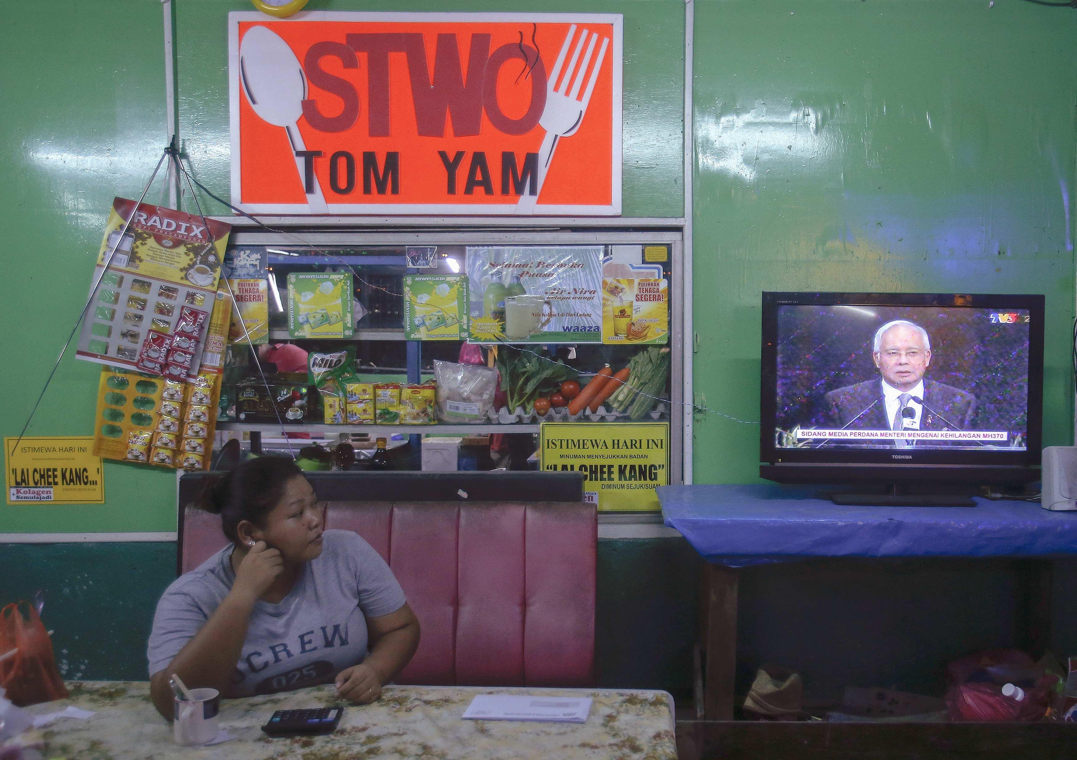 O primeiro-ministro da Malásia Najib Razak é visto na televisão, no momento do anúncio | Samsul Said/ Reuters