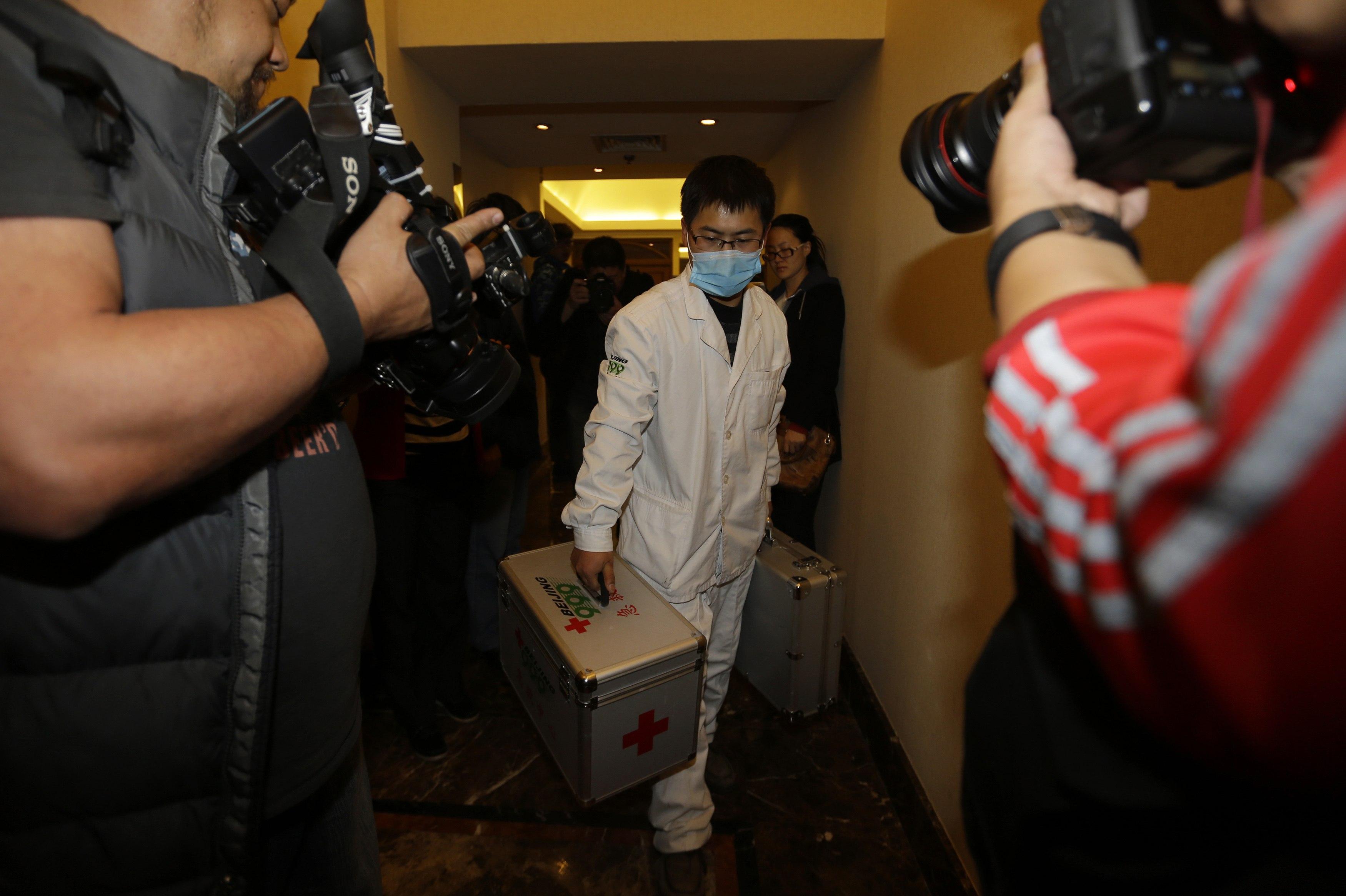 Um enfermeiro carrega um kit de primeiros-socorros enquanto atravessa o corredor do hotel onde estão hospedados os familiares dos passageiros a bordo do Malaysia Airlines MH370, em Beijing | Jason Lee/ Reuters
