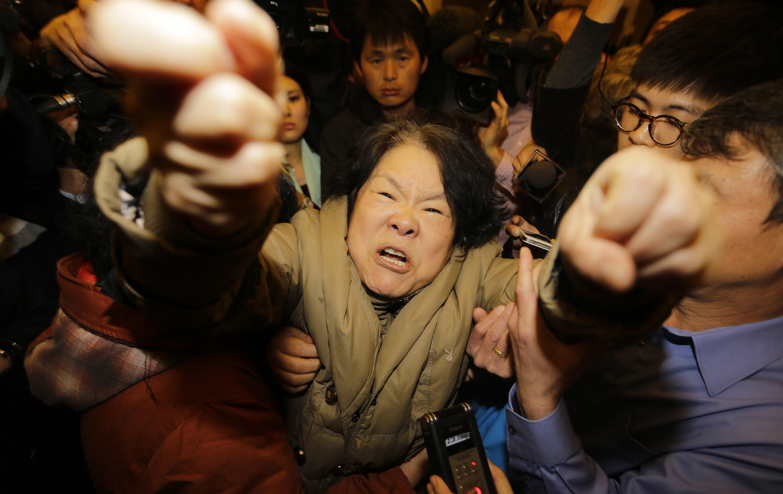 Parente de passageiro do voo grita com jornalistas no hotel em Pequim, onde familiares foram reunidos | Jason Lee/ Reuters
