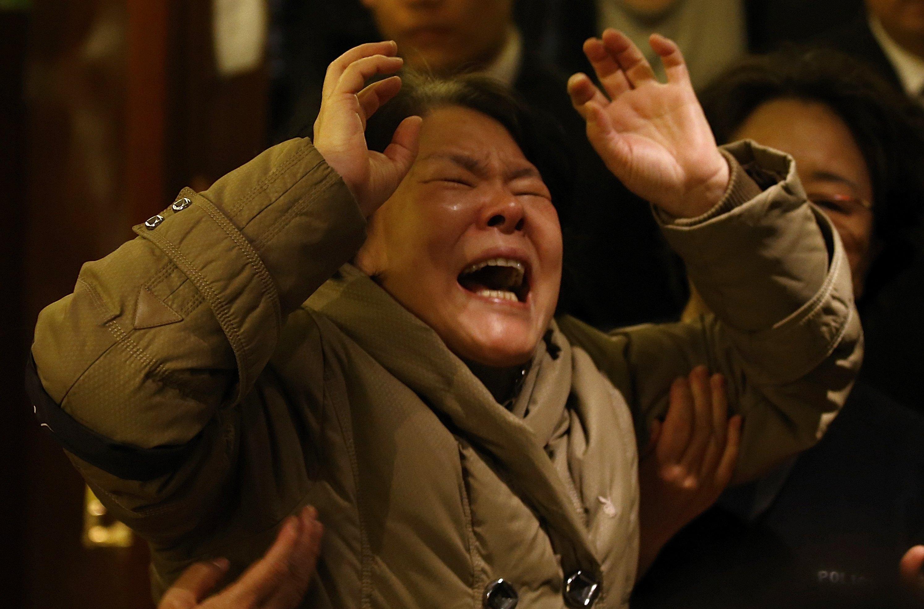 Parente de passageiro que estava a bordo do Malaysia Airlines chora após receber a notícia de que a aeronave caiu no Oceano Índico | Kim Kyung-Hoon/ Reuters