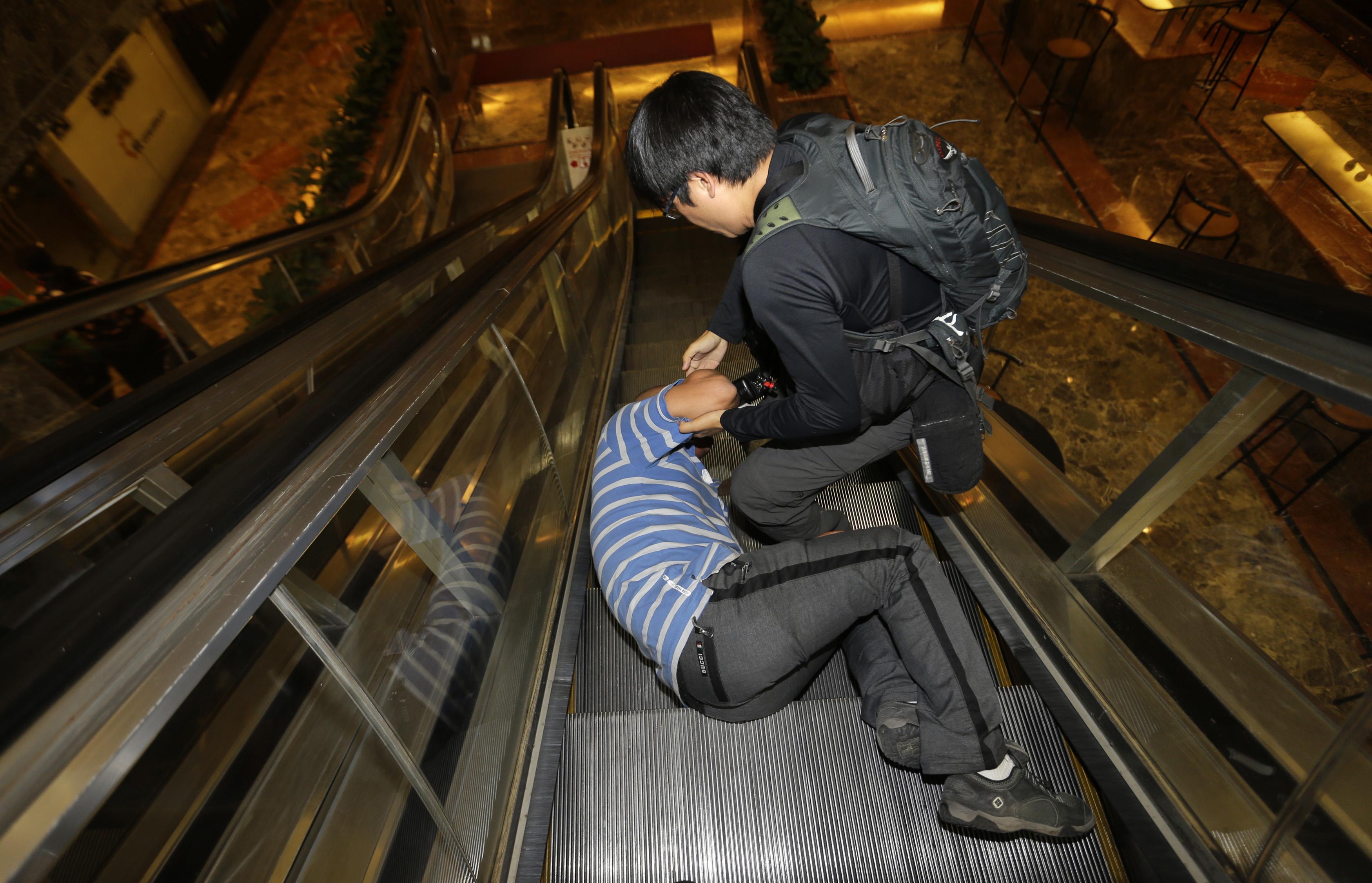 Parente de passageiro que estava a bordo do Malaysia Airlines MH370 cai na escada rolante e chora depois de assistir o pronunciamento do primeiro-ministro | Jason Lee/ Reuters