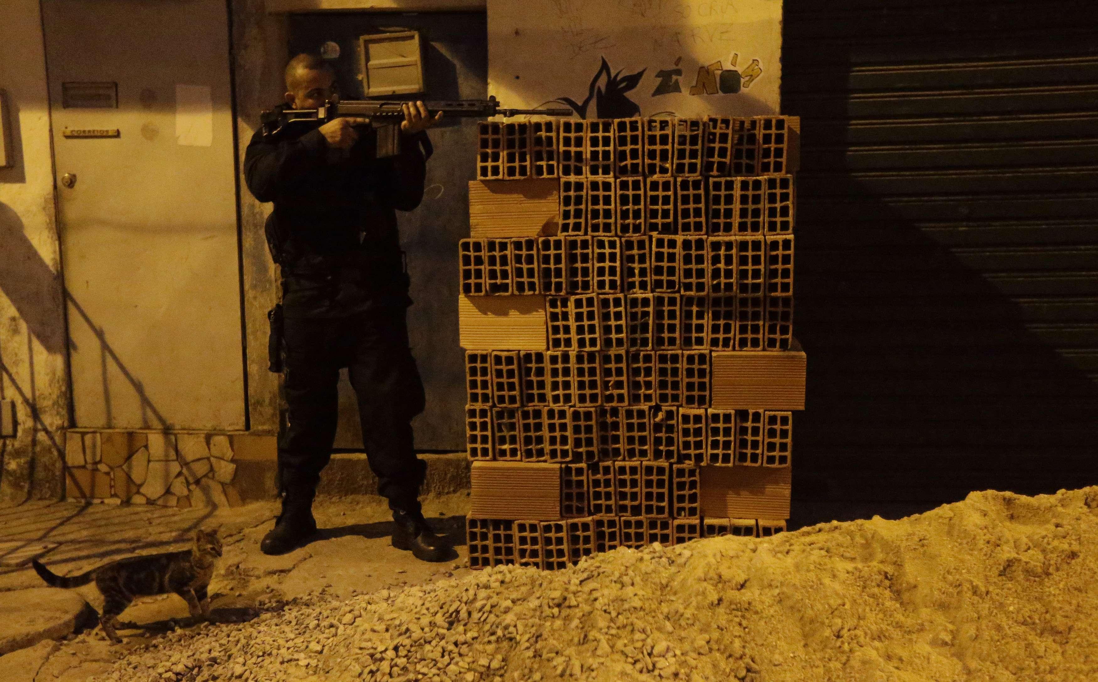 Agente das Forças de Segurança se posiciona com fuzil durante ocupação do Complexo da Maré | Ricardo Moraes/Reuters