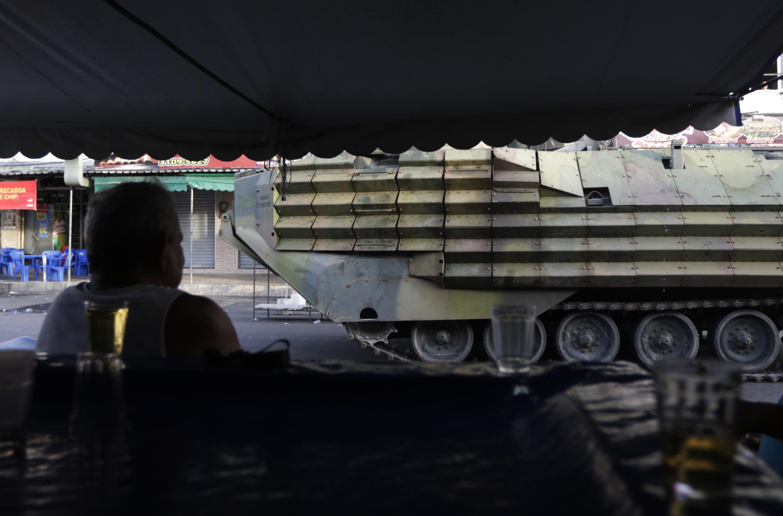 Homem observa a passagem de blindados da Marinha brasileira, utilizados na ocupação do Complexo da Maré | Ricardo Moraes/Reuters