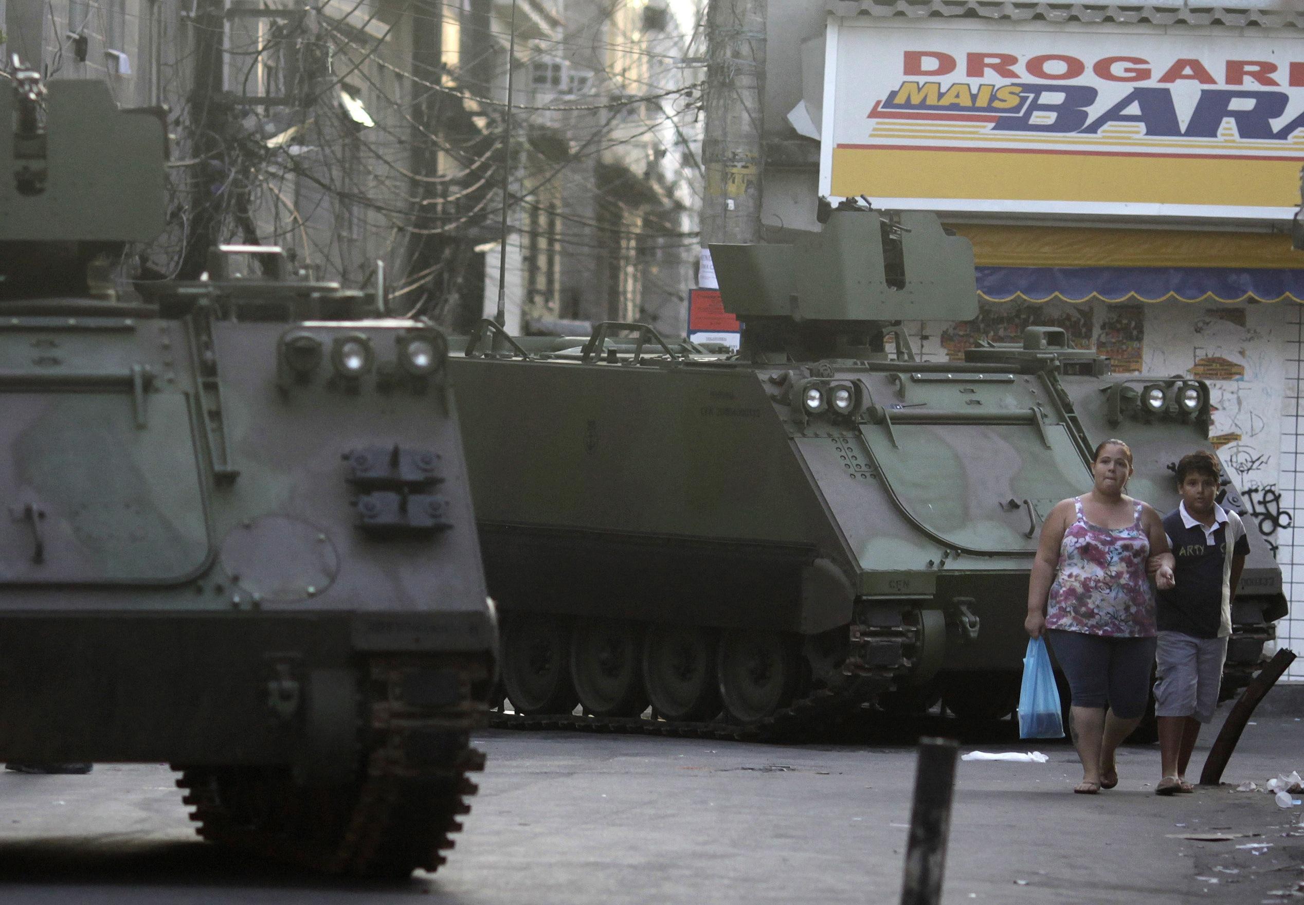 Moradores caminham próximo de blindados da Marinha brasileira, utilizados na ocupação do Complexo da Maré | Ricardo Moraes/Reuters