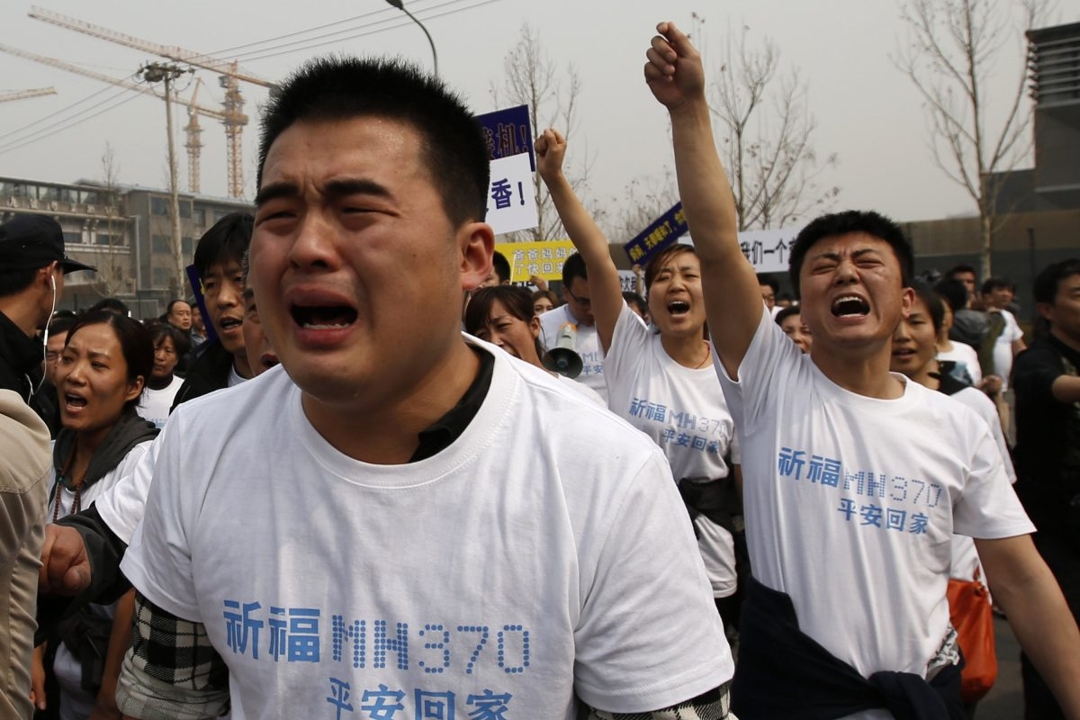 Family members of passengers onboard Malaysia Airlines MH370 cry as they shout slogans during a protest in front of the Malaysian embassy in Beijing. Imagen Por: Family members of passengers onboard Malaysia Airlines MH370 cry as they shout slogans during a protest in front of the Malaysian embassy in Beijing March 25, 2014. Dozens of angry relatives of passengers on the lost Malaysian jetliner clashed with police in Beijing on Tuesday, accusing the Southeast Asian country of