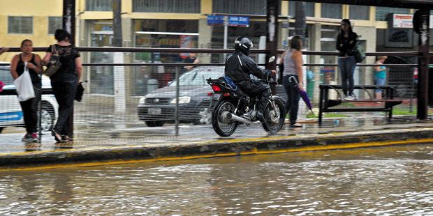 Motociclista foge de alagamento pela calçada da avenida João Dias, na zona sul | Marcelo Alves/Onipress/Folhapress