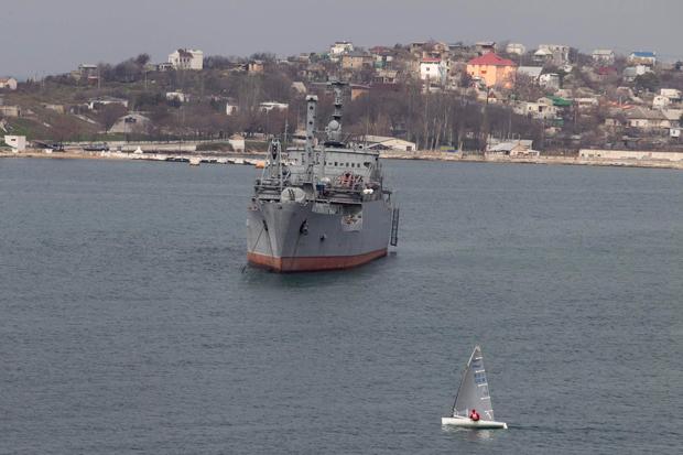 Pequeno barco passa junto a navio de guerra russo no mar Negro | Baz Ratner/Reuters