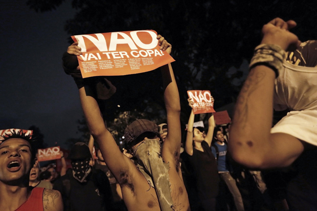 Demonstrators hold posters during a protest against the 2014 World Cup, in Sao Paulo