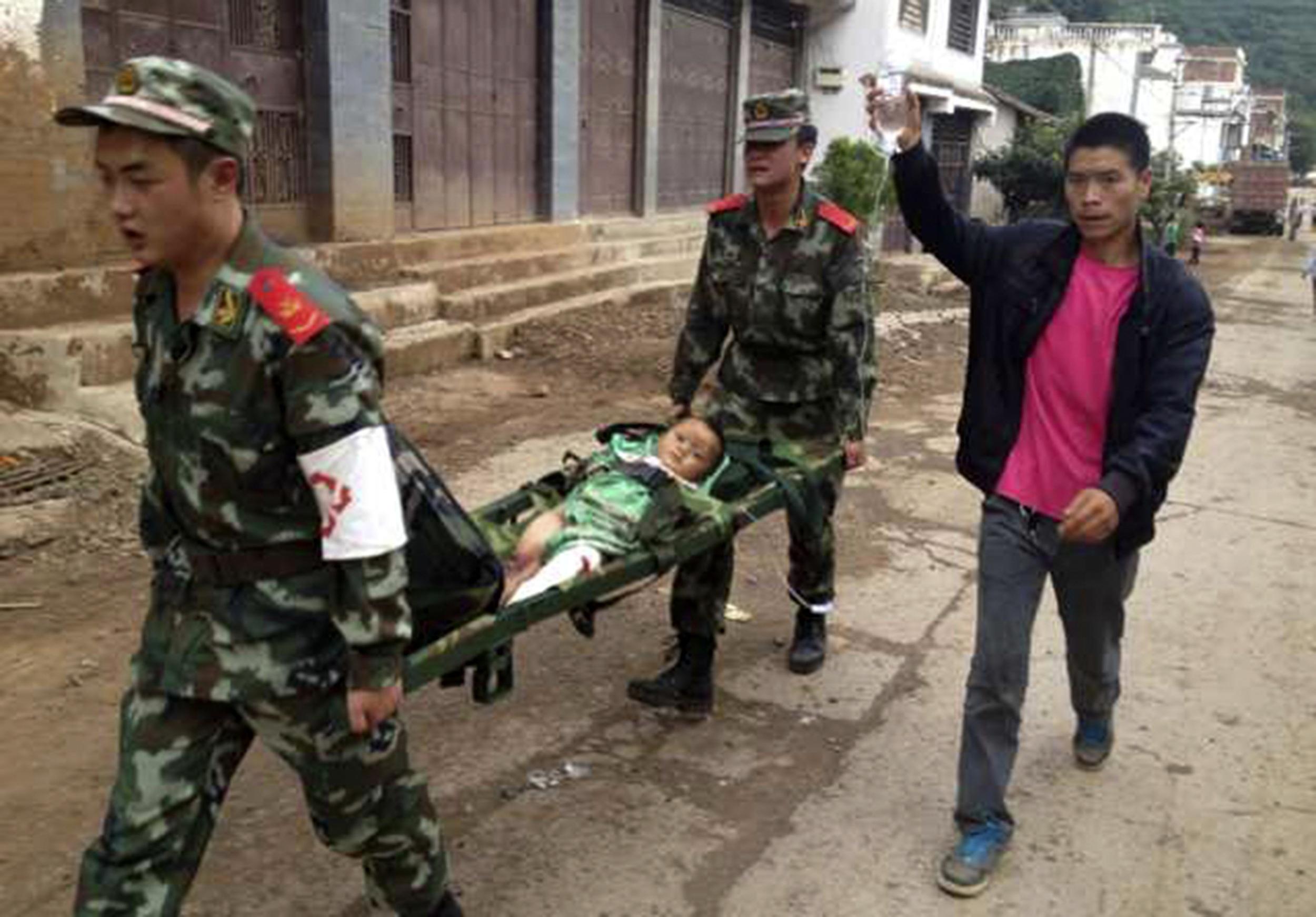 Paramilitares transportam criança ferida em terremoto na China | Reuters