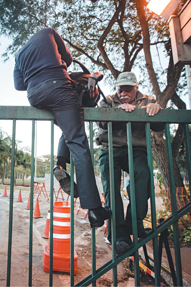 Funcionários que não aderiram à greve pulam portão | Avener Prado/Folhapress