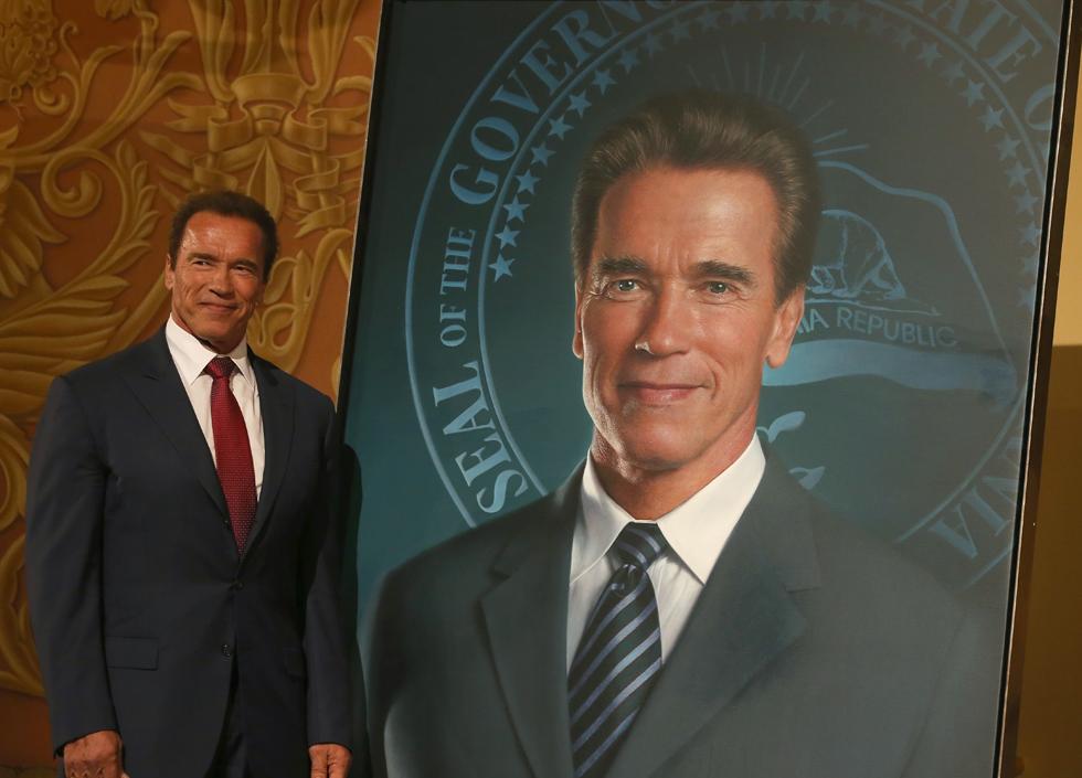 Ex-governador da Califórnia Arnold Schwarzenegger ao lado da pintura oficial | Justin Sullivan/Getty Images