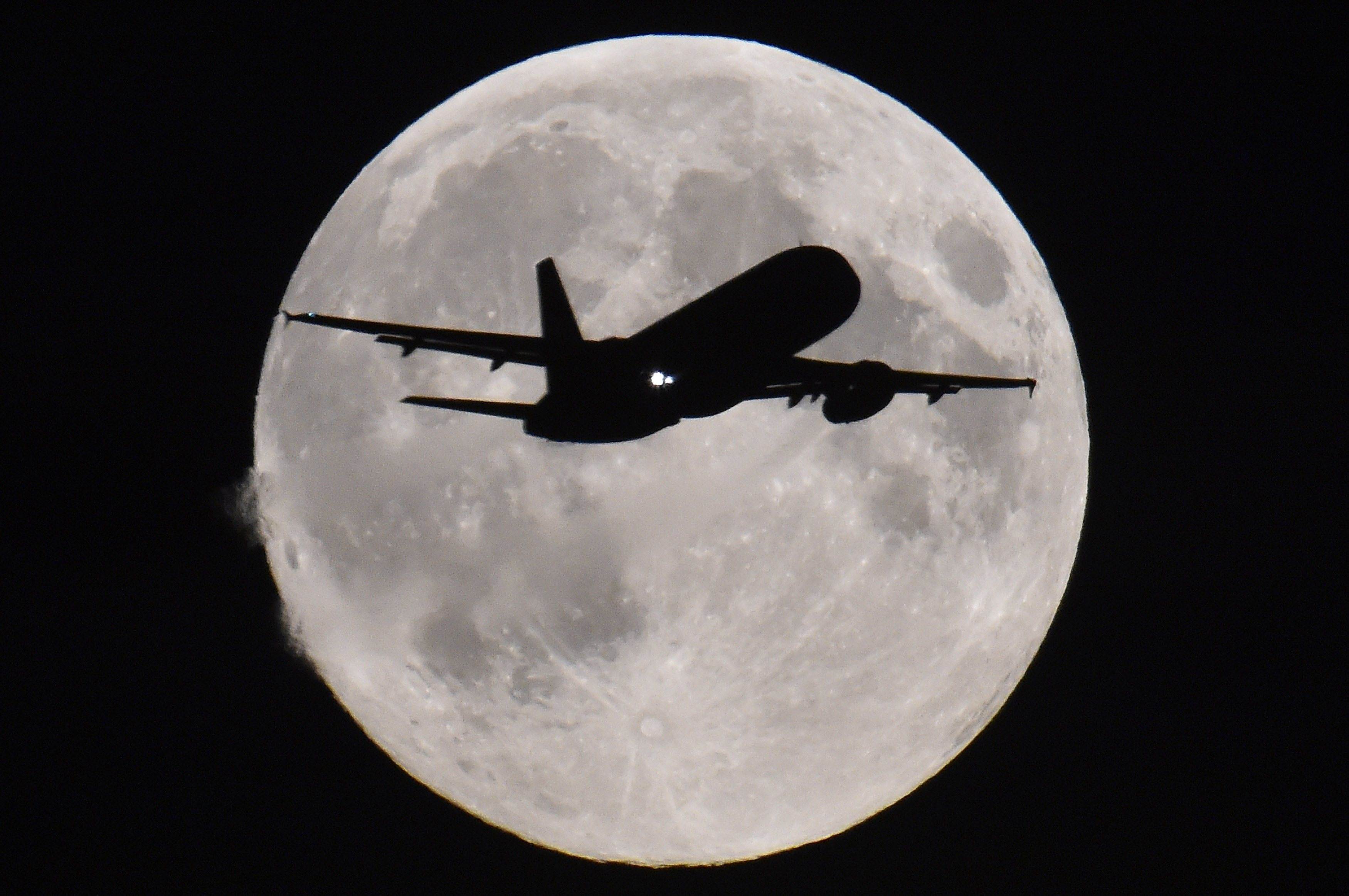 A passenger aircraft descends towards Heathrow Airport with a full moon seen behind, in west London