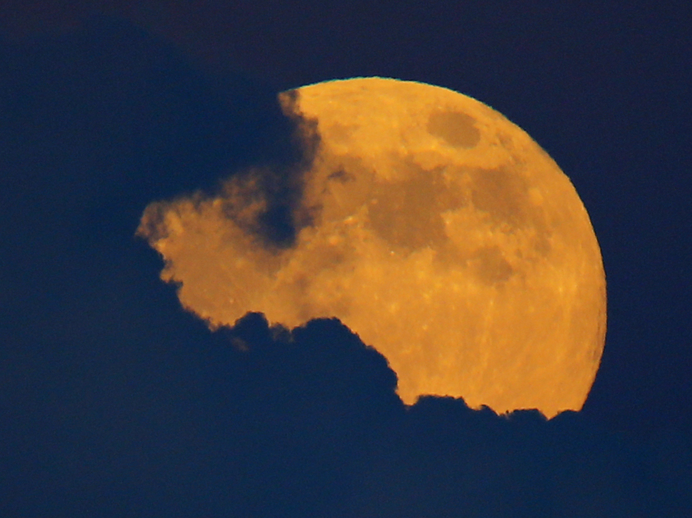A full moon, also a harvest moon, rises past thunder clouds near Encinitas, California