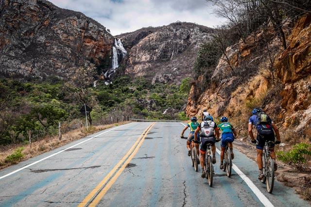 Ciclistas sobem a Serra Verde, em Rio de Contas, na 5ª etapa da ultramaratona Brasil Ride 2014, na Chapada Diamantina. No fundo, a visão espetacular de uma cachoeira | Fábio Piva/ Brasil Ride