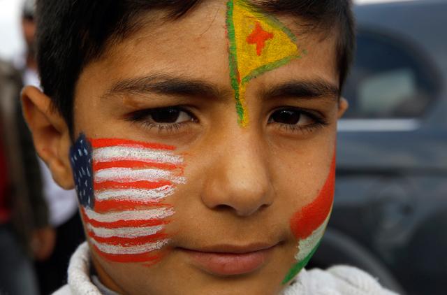 Menino curdo com a bandeira norte-americana pintada | Yannis Beharakis/Reuters