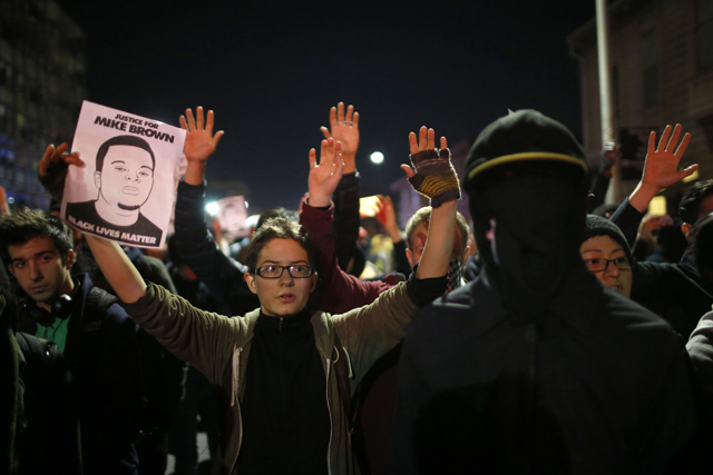 Protesters raise their hands during a demonstration in Oakland