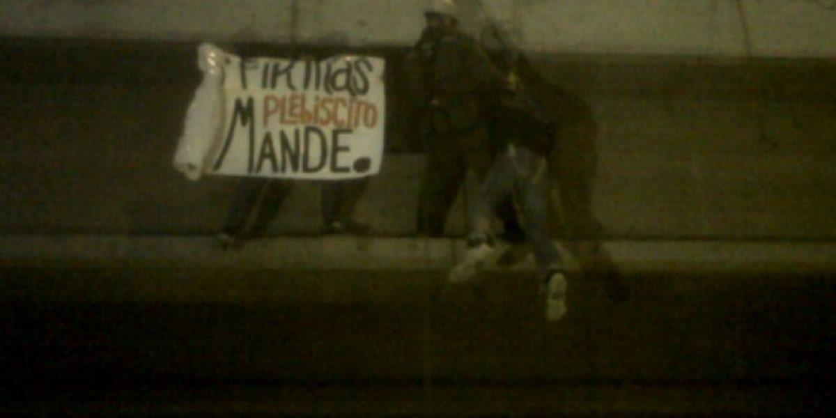 Manifestantes protestan colgados con arneses sobre rotonda Grecia