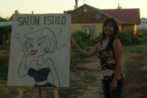 """La estilista Leonor Inzunza posa junto al cartel de su salón de belleza. Ella es la """"Yayita"""" oficial del pueblo de Cumpeo. . Imagen Por:"""