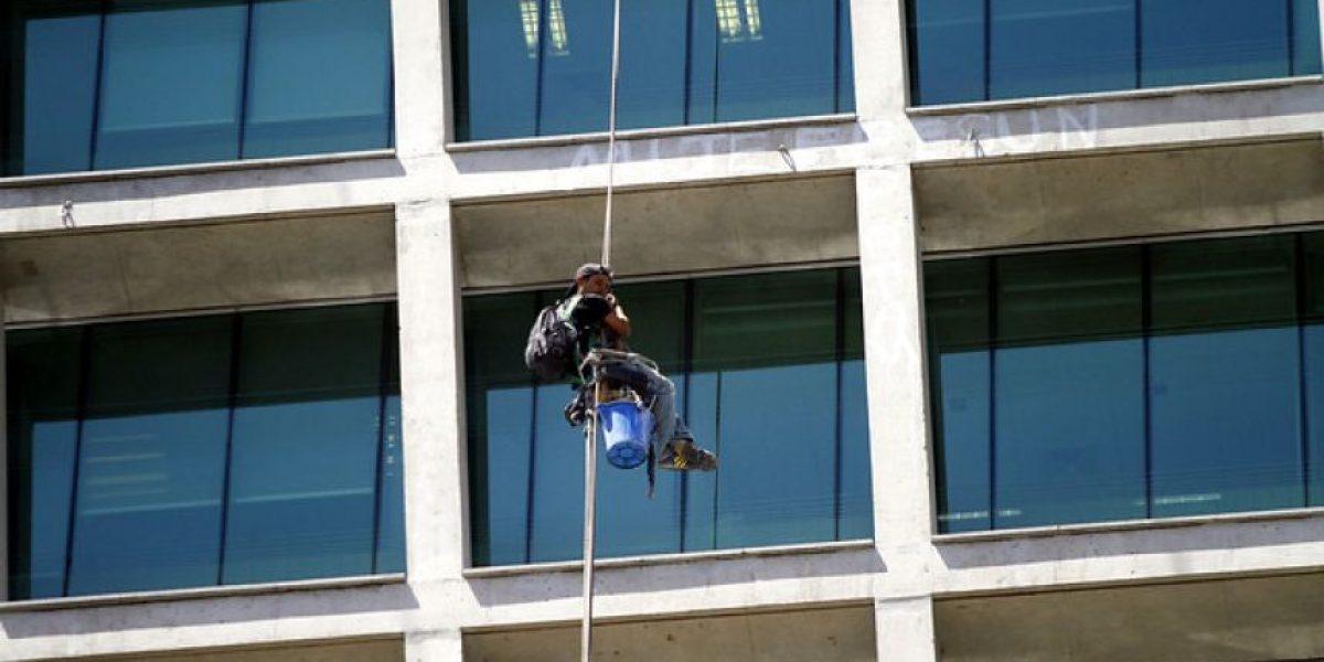 [FOTOS] Limpiavidrios protestó colgado en el piso 12 de un edificio en Las Condes