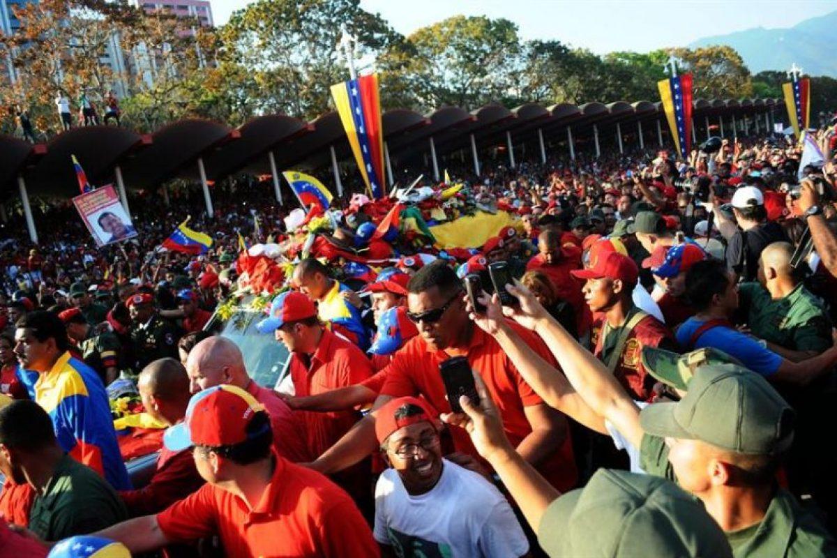 Entre cientos de miles de adherentes, la carroza que trasladaba el féretro del mandatario venezolano recorrió la principal arteria de Caracas hasta la Academia Militar, lugar donde permanecerá hasta el viernes cuando se celebrarán las honras fúnebres. Foto:EFE. Imagen Por: