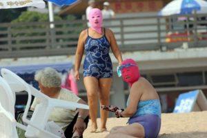 Bañistas chinos visten coloridas máscaras para protegerse de los rayos solares en la playa de Qingdao, en Shandong (China). Tener la piel bronceada significa, según creencias chinas, pertenecer a la clase campesina. Foto:AFP. Imagen Por:
