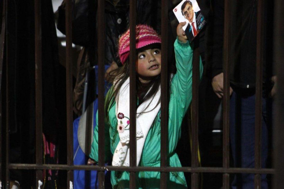 Una niña muestra una imagen del Ex-candidato UDI, en las afuera del la sede del partido político, tras la renuncia de Pablo Longueira a la candidatura presidencial. Foto:AGENCIA UNO. Imagen Por:
