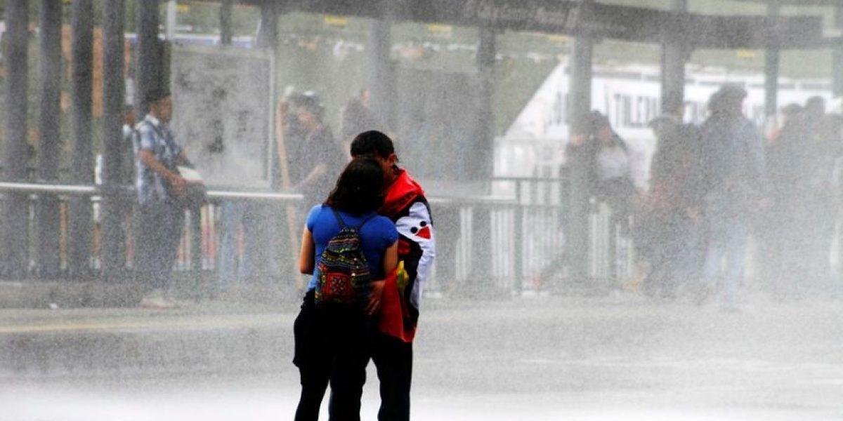 Romántico beso bajo el chorro del lanzaaguas entre las postales de la marcha