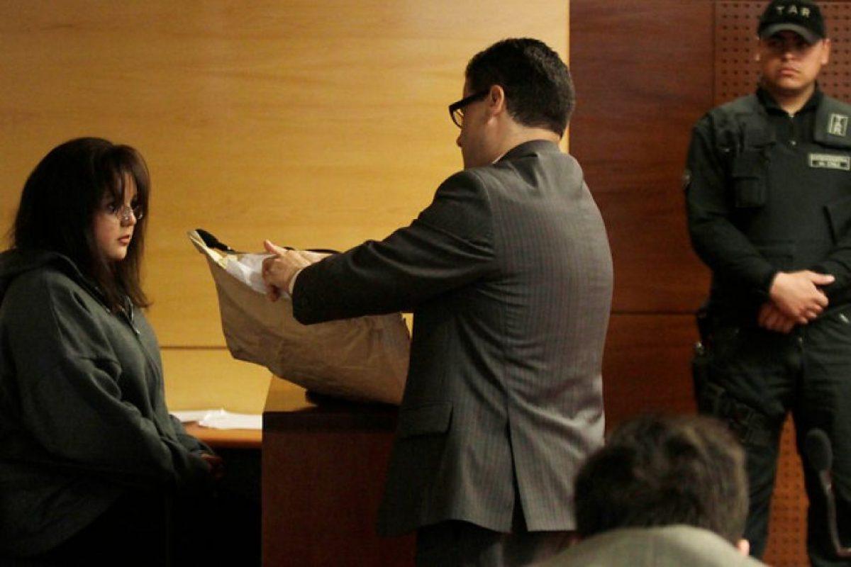 El fiscal Ernesto Vasquez,exhibe a Kateherine Perroni, hermana de la ex pareja de uno de los imputados un bolso que habría llevado Patricio Ahumada el día de los hechos. Imagen Por: