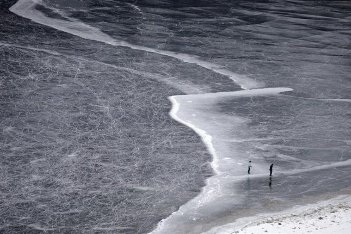 """Unas personas caminan sobre la nieve en una orilla del lago Champferer, cuya superficie está helada, en Silvaplana, Suiza, hoy, miércoles 18 de diciembre de 2013. En este lugar se produce un fenómeno conocido como """"hielo negro"""". La superficie helada es virtualmente transparente y permite ver las oscuras aguas que hay debajo. Foto:EFE. Imagen Por:"""