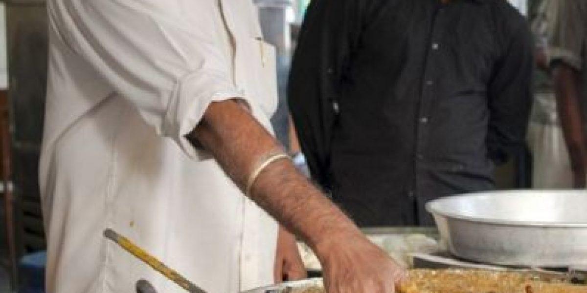 Sumerge sus manos en aceite caliente para atraer al público a su local de comida