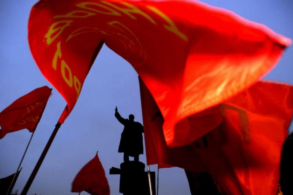 Las banderas rojas de los comunistas rusos vuelan cerca de un monumento al fundador de la Unión Soviética Vladimir Lenin durante un acto para conmemorar el 90 aniversario de su muerte, en San Petersburgo. Foto:AFP. Imagen Por: