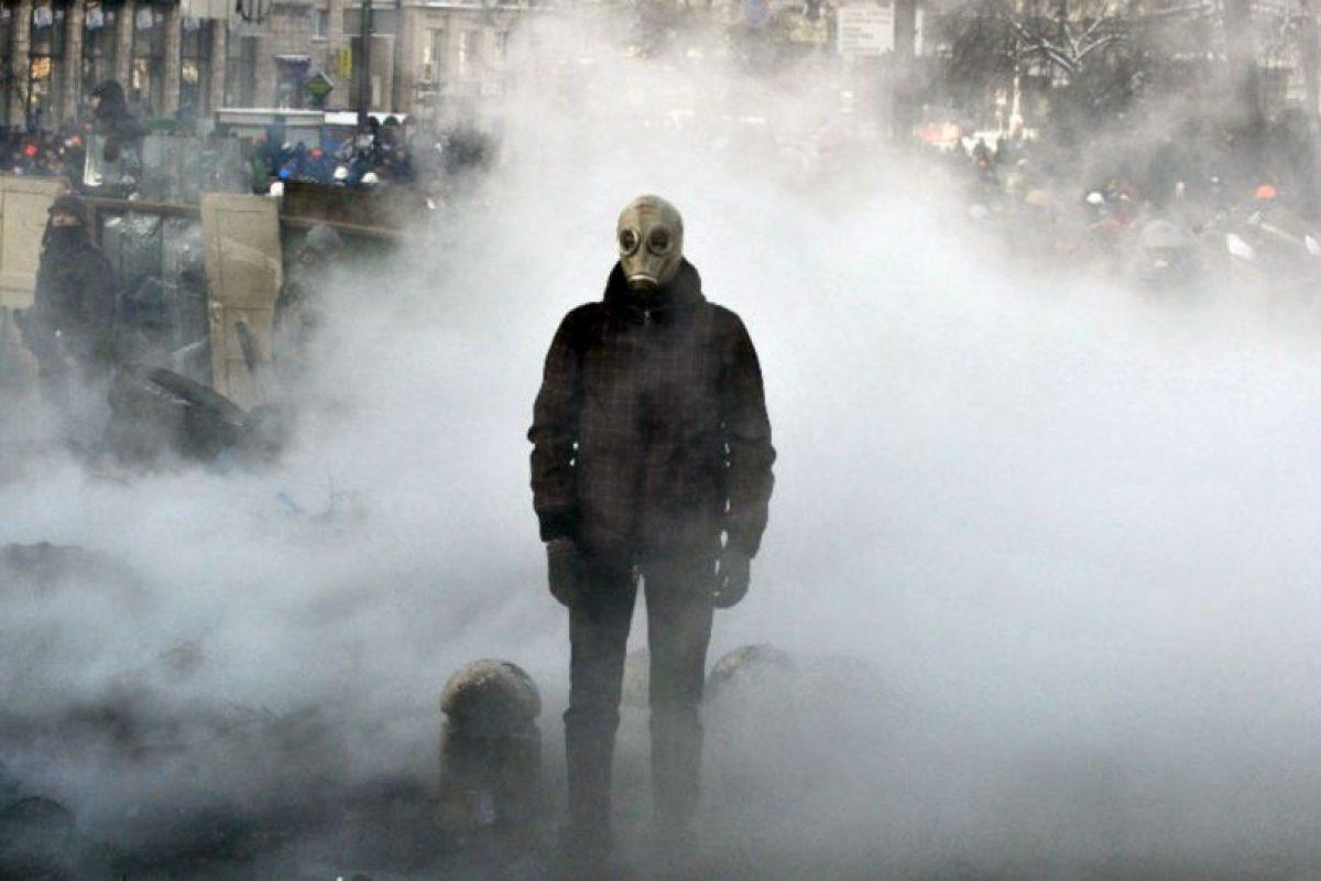 Un manifestante ucraniano que lleva una máscara de gas está en medio de un lugar donde quemaron neumáticos y basura tras los enfrentamientos entre manifestantes a favor de la UE y la policía antidisturbios, en la capital Kiev. Foto:AFP. Imagen Por: