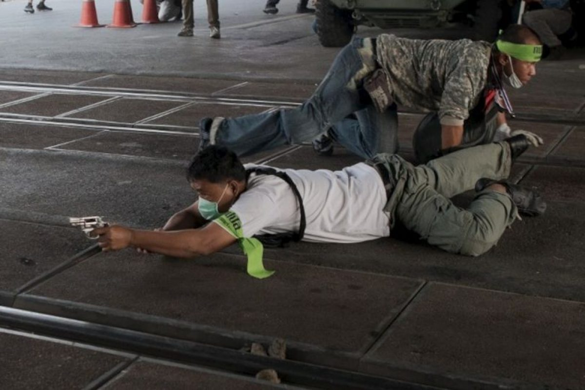 Un manifestante contra el gobierno tailandés apunta su arma antes de disparar a los manifestantes pro-electorales, en Bangkok. Foto:AFP. Imagen Por: