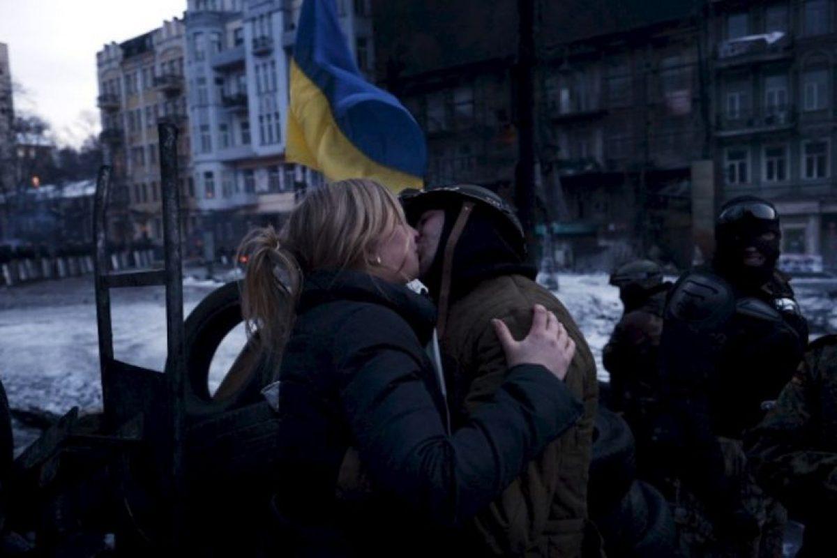 Una mujer joven besa a un manifestante contra el gobierno de Ucrania, en una barricada durante el bloque de carreteras en la capital Kiev. Foto:AFP. Imagen Por: